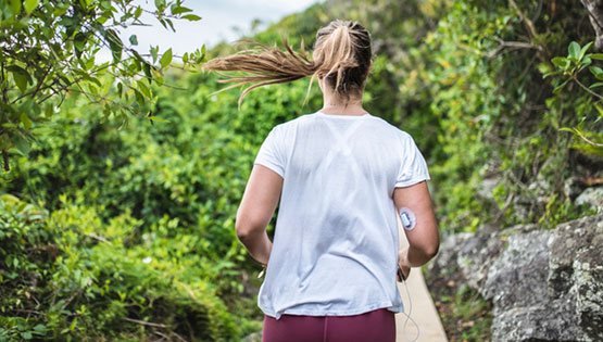 Woman running with a glucose monitor on her arm.