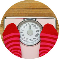 Person stepping on scale with red and pink striped socks.